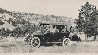 A family in their car poses among mountains in 1913.