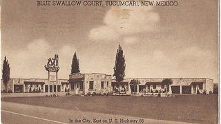 Sepia toned postcard of Blue Swallow Motel exterior and sign, circa 1941.