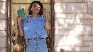 Morgan Vickers poses in front of Cactus Motel, New Mexico, with a copy of a Green Book.