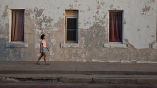 Morgan Vickers walks in front of an abandoned building in Shamrock, Texas.