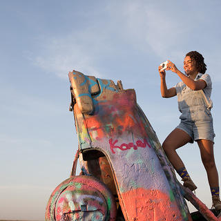 Morgan Vickers stands on top of a half-buried Cadillac at Cadillac Ranch, Amarillo, Texas, to take a Polaroid photo.