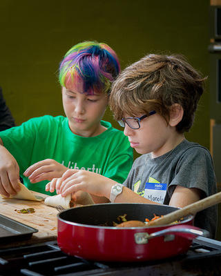 Two children cook together as part of the museum's children's programming.