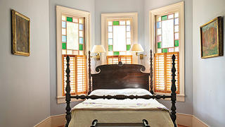 Interior photo of bedroom with Victorian stained glass inside the Isabelle Bowen Henderson House and gardens, Raleigh, North Carolina