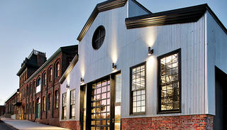 The vast complex includes the corrugated metal shop and the main brick building with a cupola.