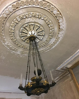 The chandelier and ceiling medallion in the ballroom show their age.