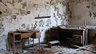 One of the rooms at Eastern State Penitentiary shows a desk and peeling white and green paint.