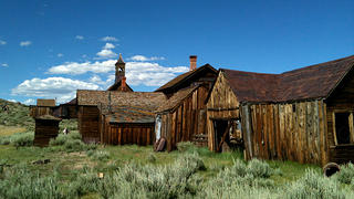 The exteriors of structures at Bodie, which shows weather-washed wood that tilts.