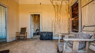 This living room still has the furniture and wallpaper, though water stains show its decay.