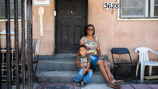 Jacqueline Story with her grandson in front of 3628 Frow Avenue.