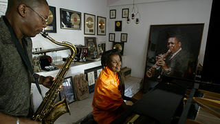 Alice Coltrane plays on the Steinway piano her husband gave her in 1964, and her son, Ravi, plays the saxophone in front of a photograph of John Coltrane (2004).