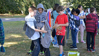 Sleepy Hollow Middle School students craft a creepy scarecrow during this Halloween event.