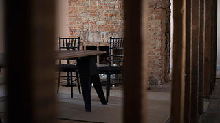 Inside the slave quarters on the second floor of the adjoining service wing with chairs, table, and brick fireplace.