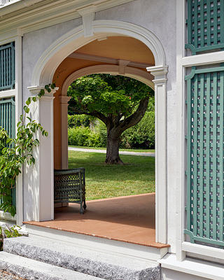 Exterior stucco archway with green lattice fencing.