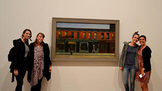 Nighthawks standing in front of a painting.