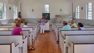 Interior of African Meeting House with tour group.