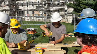 Working on cutting plywood with the Centre Family Dwelling Behind.