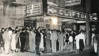 Line to Club Harlem with Clifton's neon sign at night.