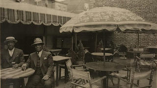 Interior of Austin's Rose Garden, with two African American men sitting at a patio table and enjoying a drink.