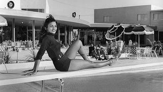 "Theodora ""Dolcinia"" Boyd relaxes on the diving board at the Moulin Rouge pool, May 20, 1955."