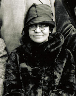 Annie Malone in a black fur coat and a hat with a ribbon.