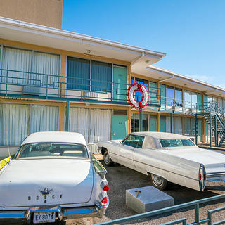Exterior of the Lorraine Motel in Memphis, Tennessee, with two vintage cars parked in front of the building.