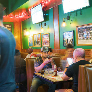 People gather inside a dive bar with drinks.