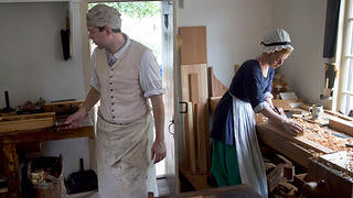 A women and man at work in a carpenter and joiner shop in Colonial Williamsburg.