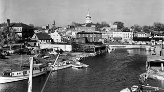Historic image of Annapolis' City Dock with boats, buildings, and water.