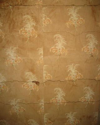 Peeled, faded vintage wallpaper with flower design.