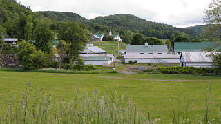 Spring Road in Tunbridge, Vermont, with green fields, forests, and farm buildings.