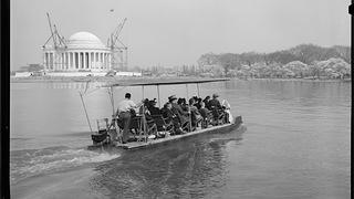 Tourists on flat boat in front of Jefferson Memorial under construction in 1941.