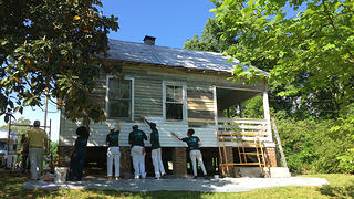 Five HOPE Crew corpsmembers paint the exterior of Nina Simone's childhood home white.