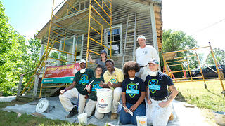 Members of HOPE Crew stand in front of Nina Simone's unpainted childhood home with painting materials.