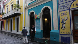 Blue and yellow buildings on an Old San Juan street, with two men standing outside and chatting.