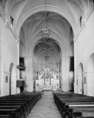 Black and white church interior with pews and alter.