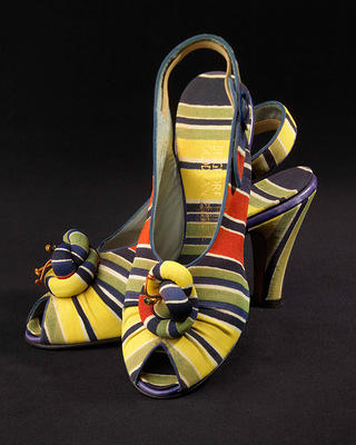 Pair of black, blue, red, yellow, green and white striped open high heels with strap and elastic band, buckle at side. Open, pointed toe with flower form and same material inside.