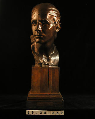 "Bronze head of ""Italian Youth."" Male with scarf covering head and tied at nape. Subject's head is held up and turned slightly to his right. Rectangular wood base with step-molding."