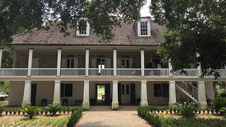 The facade of a large, two-story plantation home painted white.