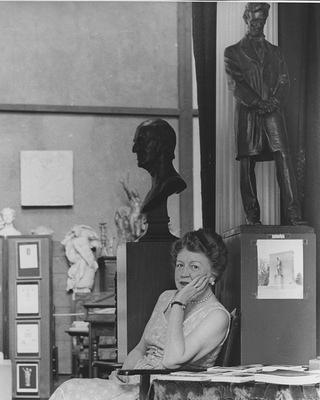 Black and white photo of Margaret French Cresson sitting in front of a Lincoln statue in Chesterwood's studio, possibly from the 1950s.