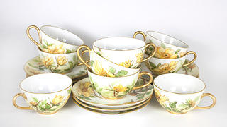 Cups and saucers painted with bright yellow flowers are stacked on top of each other.