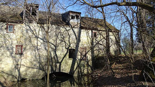 The exterior of the historic grist mill as seen in 2018.