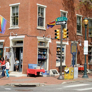 A street view of the store's brick facade. Two tables of books sit outside either side of the front door of the store; shoppers walk past; and a pride flag hangs from the building