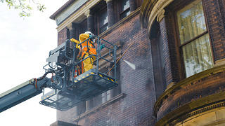 Three crew members stand in a cherry picker and power wash the brick exterior.
