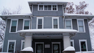 """The front of the Quaker meeting house, blanketed in snow, displays a sign that reads """"Friends Meeting House."""""""