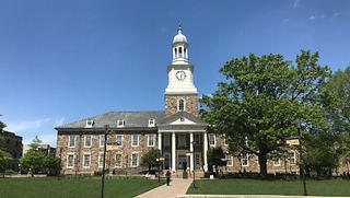 Holmes Hall is a brick building with four white columns by the front entrance. The hall features a clock and bell tower extending up in the center of the building.