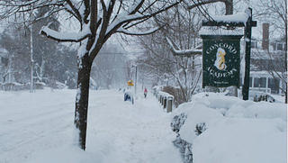 A Concord Academy sign stands on a street, blanketed in snow.