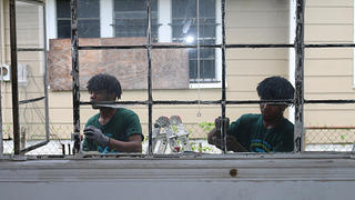 HOPE Crew participants restore the windows of the Bethel Baptist parsonage