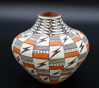 Color photo of one of the pots available for purchase at Acoma Sky City's online shop. This pot features and black, white and orange checkerboard pattern with black lighting bolts.