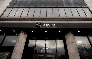 Exterior of a modern building in New York City with a sign that says Carver Federal Bank.