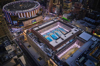 Exterior, overhead view of Moynihan Train Hall and Madison Square Garden. Both structures are lit up and glowing with energy.